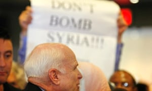 A crowd member holds up signs against military action in Syria  as US Senator John McCain speaks with constituents during a town hall meeting in Phoenix.