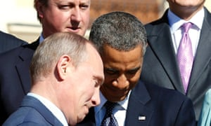 Russian President Vladimir Putin walks past  Barack Obama during a group photo at the G20 Summit.