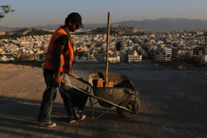 A worker repairing a pavement pushes a wheelbarrow as the ancient Acropolis Hill is seen in the background above a sea of apartment buildings in Athens, on Friday, Sept. 6, 2013.