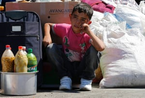 A Syrian boy sits beside his family's belongings as they wait for a vehicle to pick them up after entering Turkey from the Turkish Cilvegozu border gate, located opposite the Syrian commercial crossing point Bab al-Hawa, in Reyhanli, Hatay province, September 6, 2013.