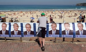 A man leans against political posters outside a polling booth at Sydney's Bondi Beach on September 7, 2013, in Australia's general election.