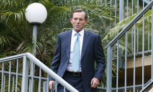Tony Abbott emerges in a suit after finishing his morning bicycle ride