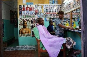 Goran Tomasevic: A customer sits in a barber shop in Lamu town, the capital of Lamu, an isla