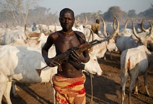 Goran Tomasevic: A man from the Dinka tribe holds his AK47 rifle at a cattle herders' camp n