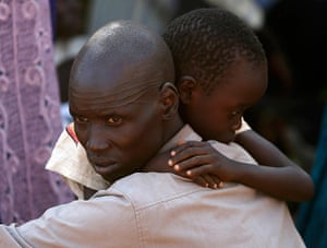 Goran Tomasevic: An internally displaced man holds his son inside a United Nations compound