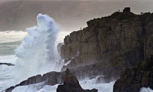 Members of the public are dwarved by huge waves on a clifftop at Land's End in Cornwall