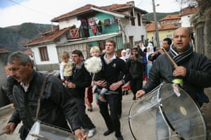 A Roma band leads guests to a lunch celebration on the second day of the her two-day weddin