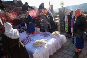 Family and friends of the bride arrange items of her dowry outside.