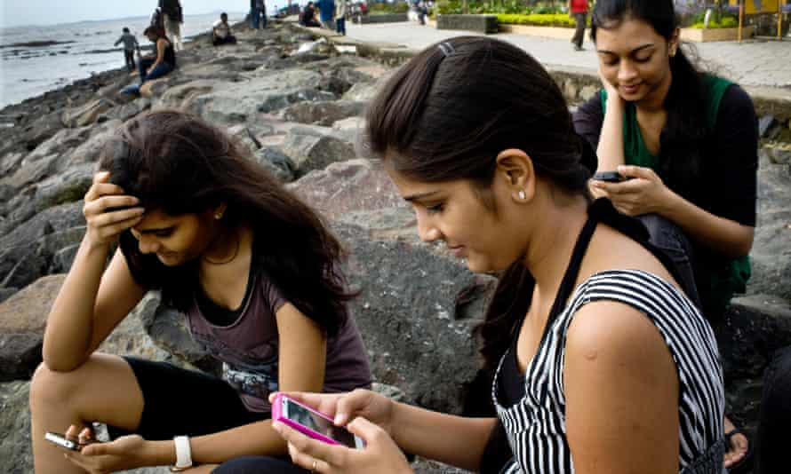 India college students check Facebook accounts on smartphones in Mumbai, India. The country will gain more than 200m new smartphone users in 2014, taking total use there to over 360m according to a new forecast.