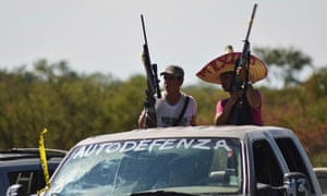 Vigilantes stand on a pick-up truck on the outskirts of Paracuaro, Michoacán state.