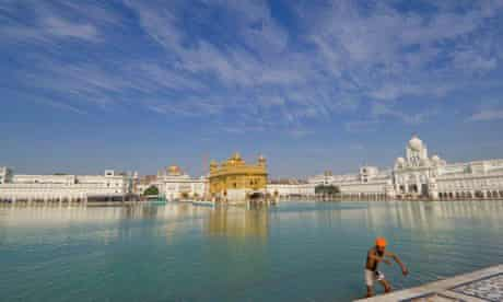 A Sikh pilgrim bathes in the sarovar of the Golden Temple of Amritsar, India