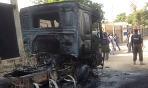 Police guard a burnt truck after an attack by Boko Haram Islamists in Maiduguri, Nigeria, last month