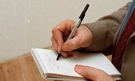 close-crop of a critic's hands and pen and pad
