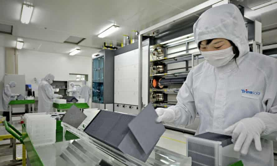 A masked lab worker sorts silicon wafers at the manufacturing centre of solar cells, Changzho, China.