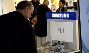 A man looks at a Samsung smartphone in a store. The company is looking to boost sales of its top-end devices.