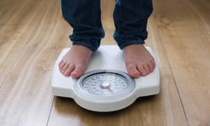 Someone stands on bathroom scales; the Body Mass Index is a simple, but also simplistic, way to measure health and fitness.