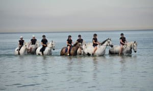 South Australia police officers take police horses for an early morning swim. The heatwave is giving Adelaide five consecutive days above 40C, its third longest hot spell.