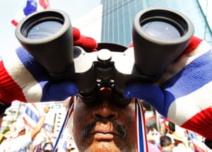The anti-government protests continue in central Bangkok. A man uses a pair of binoculars to keep an eye on the police.
