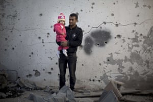 A Palestinian man holds his daughter in front of a damaged building following overnight Israeli air strikes in Gaza City.