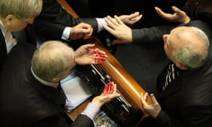 Ukrainian pro-government lawmaker Vladimir Malyshev, left, wipes the blood from his face after a scuffle.
