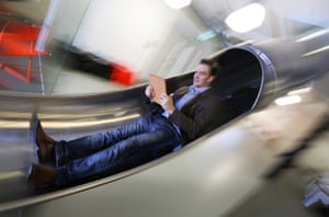 James Avery, manager at the Works in Folkestone, Kent, an innovative business centre, checks his tablet computer as he travels between the floors of the offices using a slide which was installed for staff last summer.
