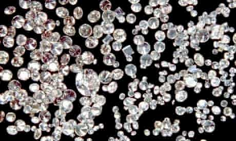 Assorted cut and polished diamonds on a black velvet cloth.