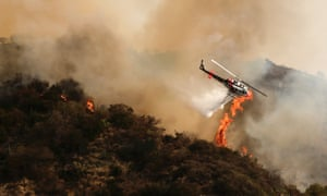 A helicopter drops water over a wildfire burning out of control near homes in the dangerously dry foothills of the San Gabriel Mountains , California.