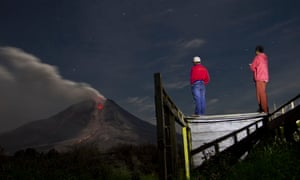 Villagers from nearby Jraya village, in North Sumatra, Indonesia, watch Mount Sinabung spewing lava and ash into the night sky.