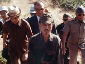 Hiroo Onoda, still carrying his sword, walks out of the Philippine jungle to surrender in 1974.