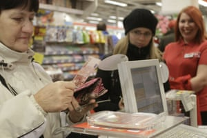 A shopper checks her euro banknote change at the checkout till in a supermarket in Riga, Latvia 1 January 2014 as the country joins the eurozone. Latvia became the 18th country to join the single currency union.