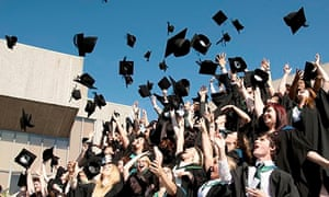 Aberystwyth university students graduating on graduation day, throwing their caps in the air, UK