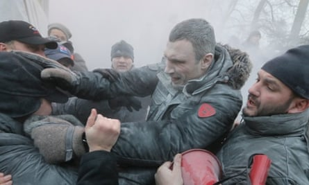 Opposition leader and former WBC heavyweight boxing champion Vitali Klitschko, center, is attacked and sprayed with a fire extinguisher as he tries to stop the clashes between police and protesters  in central Kiev, Ukraine.
