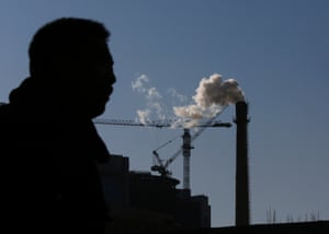 A man is silhouetted against cranes at a construction site and a chimney of a heat supply plant in Beijing, January 20, 2014.