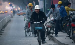 This picture taken on January 15, 2014 shows a group of Chinese workers riding bicycles outside a construction site in Beijing.