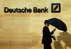 A man walks past Deutsche Bank offices in London in this December 5, 2013 file photo.