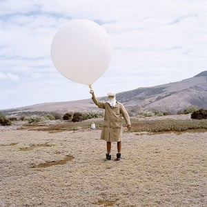 Big Picture - Empire: man stands on dusty landscape holding balloon