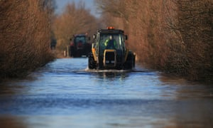 A tractor drives through flood water on the Somerset Levels near Langport. Large areas of Somerset still remain under water