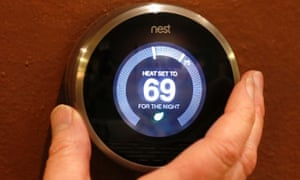 A Nest thermostat being adjusted in a home.