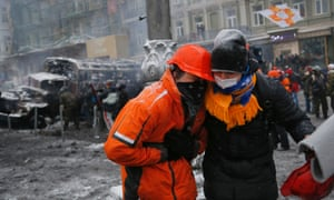 A wounded protester is assisted.