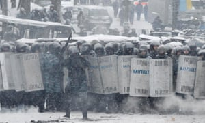 Ukrainian riot police line up in front of pro-European protesters.