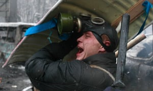 A pro-European protester reacts while taking cover.
