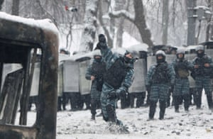 A Ukrainian riot police officer throws a molotov bottle during clashes