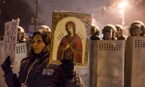 A woman holds an image of a religious icon and a sign that reads: You all are my children. I love you all! on a third night of demonstrations.