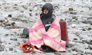 A man wrapped in a blanket sits on the carriageway in Grushevsky Street where the cobblestones have been removed by the demonstrators.