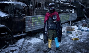 Anti-government protester stand next of a charred police truck during standoff with riot units on Hrushevskoho street after consecutive nights of clashes.