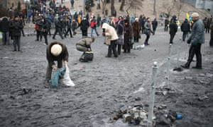 Demonstrators collect cobblestones in Grushevsky Street to use them against riot police.