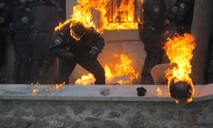 A member of the Ukrainian riot police caught in the flames of gasoline bombs hurled by anti-government protestors.