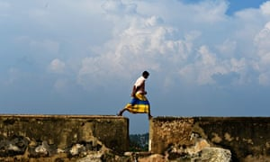A Galle resident walks on the centuries-old flood defence walls, in 2013.