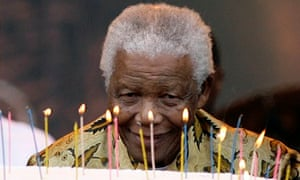 Nelson Mandela blows out candles on a cake at the Loftus stadium in Pretoria