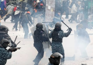 A riot police officer, right, and an Interior Ministry member attack pro-European protesters.